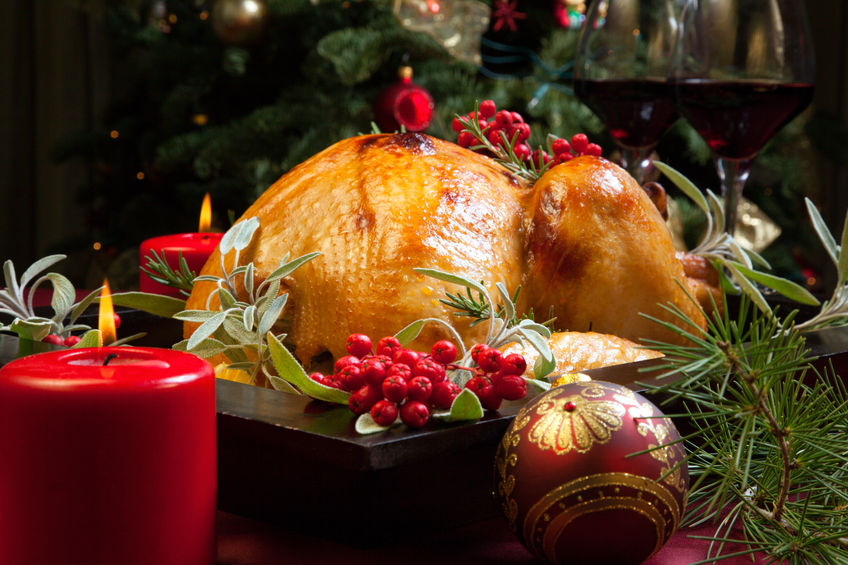 47068296 - roasted turkey garnished with sage, rosemary, and red berries in a tray prepared for christmas dinner. holiday table, candles and christmas tree with ornaments.